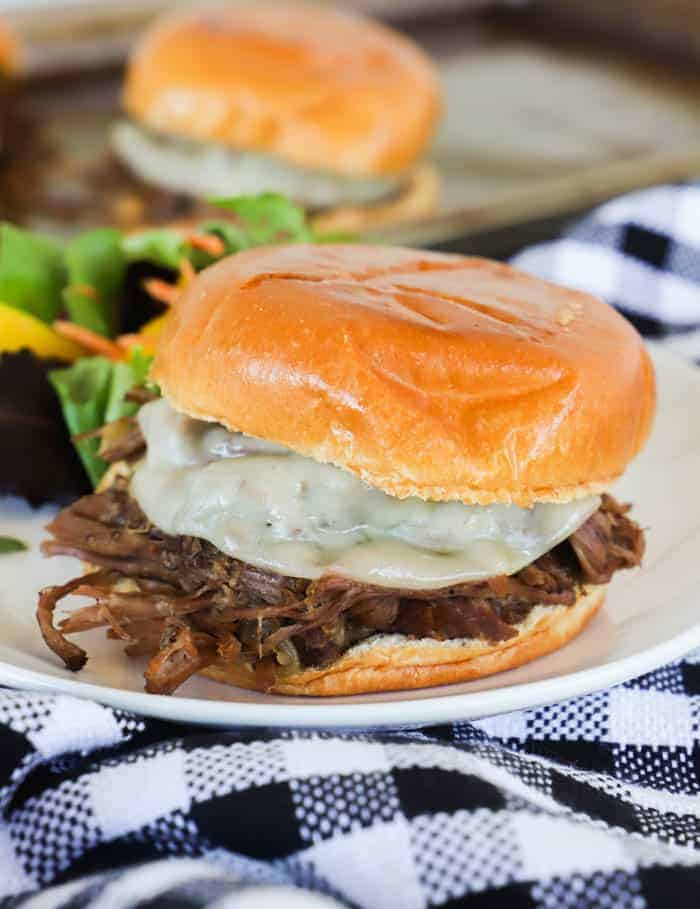 Slow Cooker Shredded Beef Sandwiches on a white plate with salad