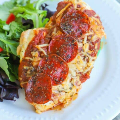 Pizza Stuffed Chicken on a white plate with a salad