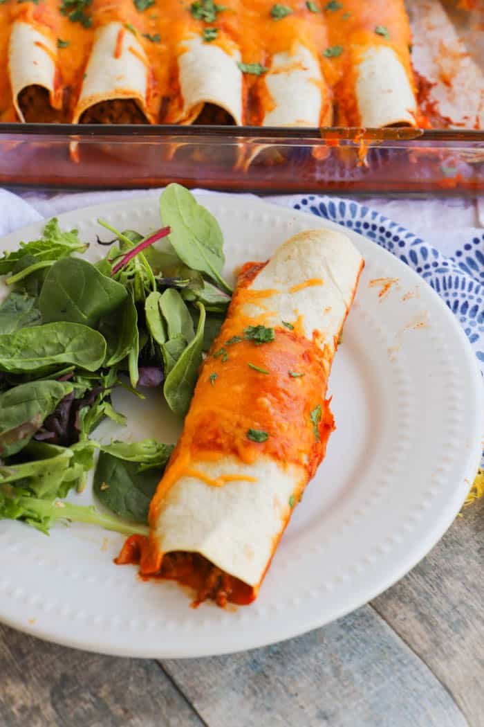 Easy Beef Enchiladas in a white plate with a salad on the side