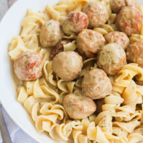 Slow Cooker Swedish Meatballs with noodles in white bowl