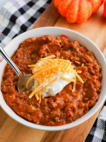 slow cooker pumpkin chili recipe in a bowl with spoon