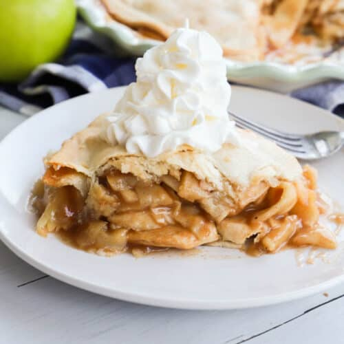 apple pie on a white plate with whipped cream