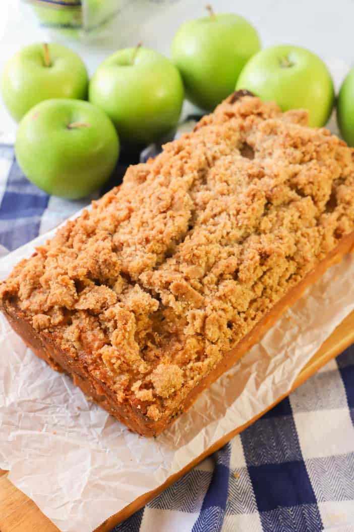 Dutch Apple Pie Bread on a wooden cutting board and apples