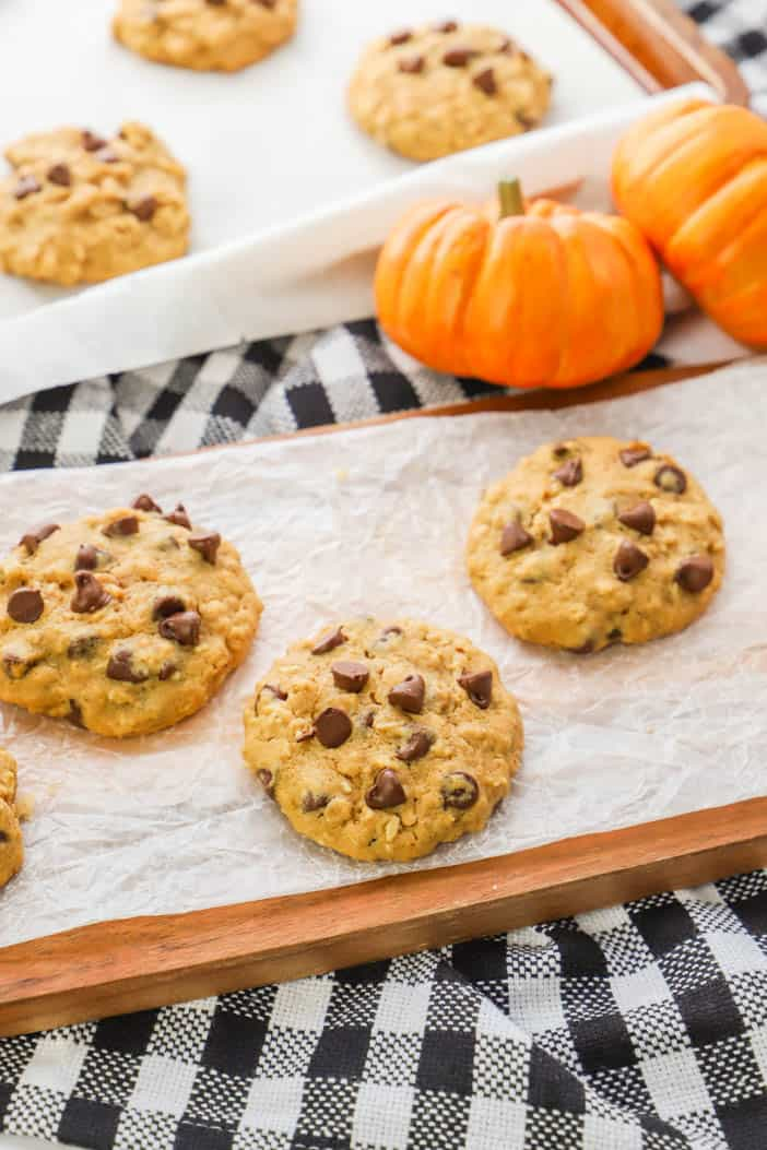 Pumpkin Oatmeal Chocolate Chip Cookie with pumpkins in the back