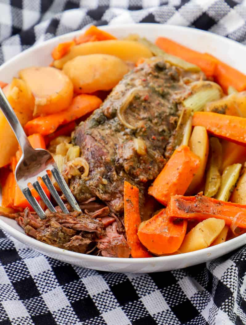 pot roast in a white bowl with veggies and a fork