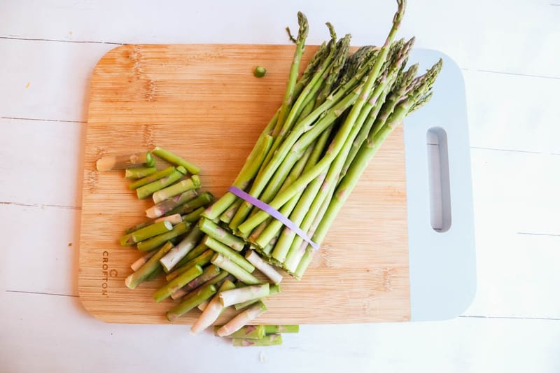 Asparagus with ends cut off on cutting board