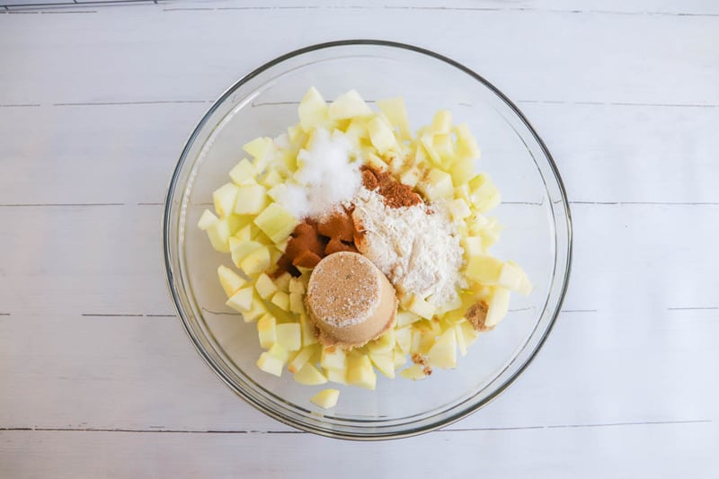 apples with spices and sugar in clear bowl