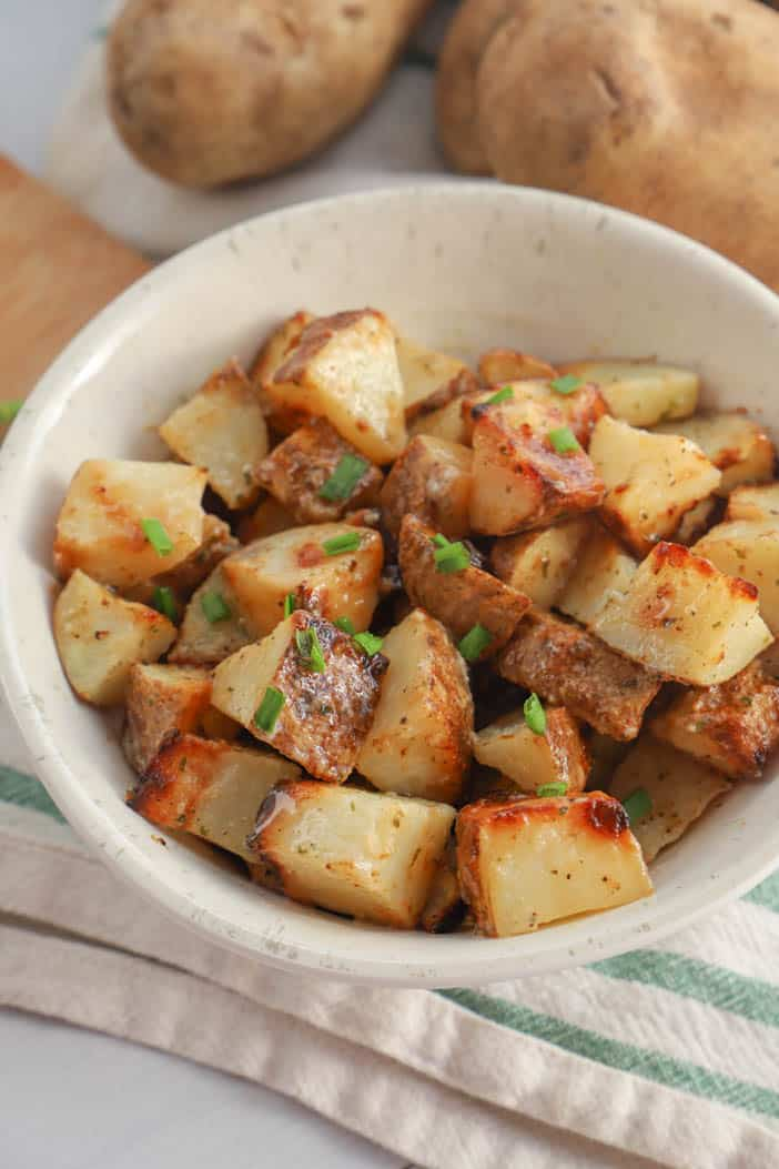 close up picture of potatoes in a bowl sprinkled with green chives