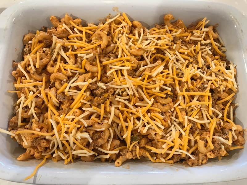 taco mac casserole in white casserole dish with shredded cheese