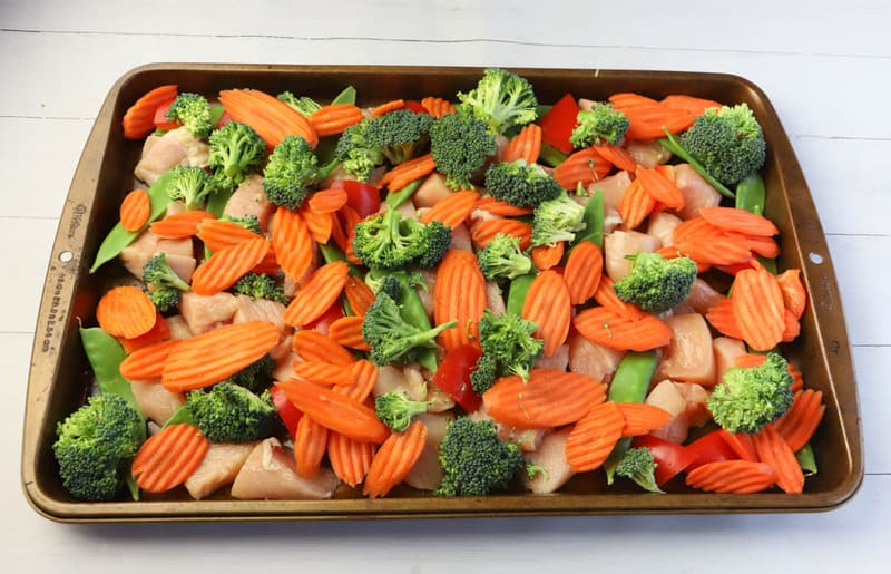veggies and chicken on sheet pan before baking