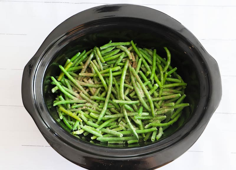 adding seasoning to the green beans