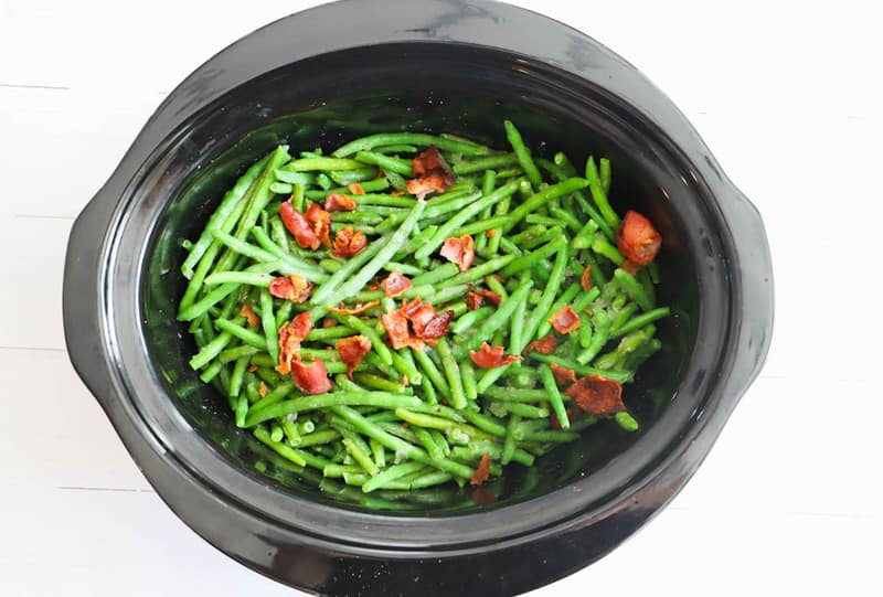 adding bacon to the slow cooker with green beans