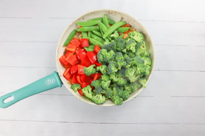 adding more veggies to a skillet