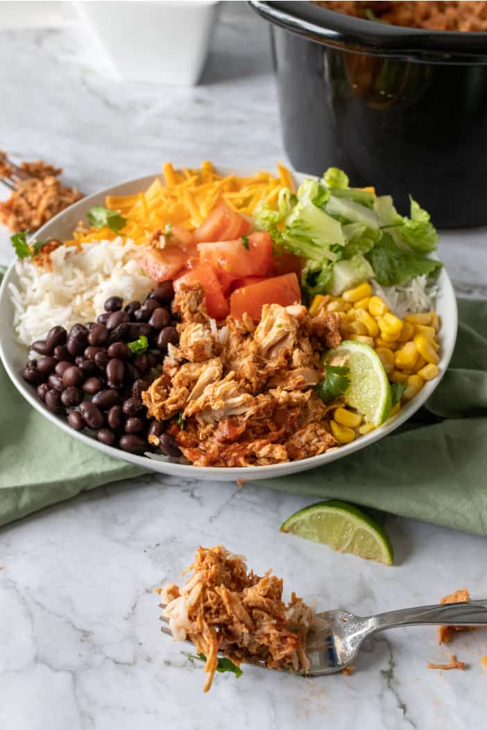 Slow Cooker Shredded Mexican Chicken topped with all the ingredients