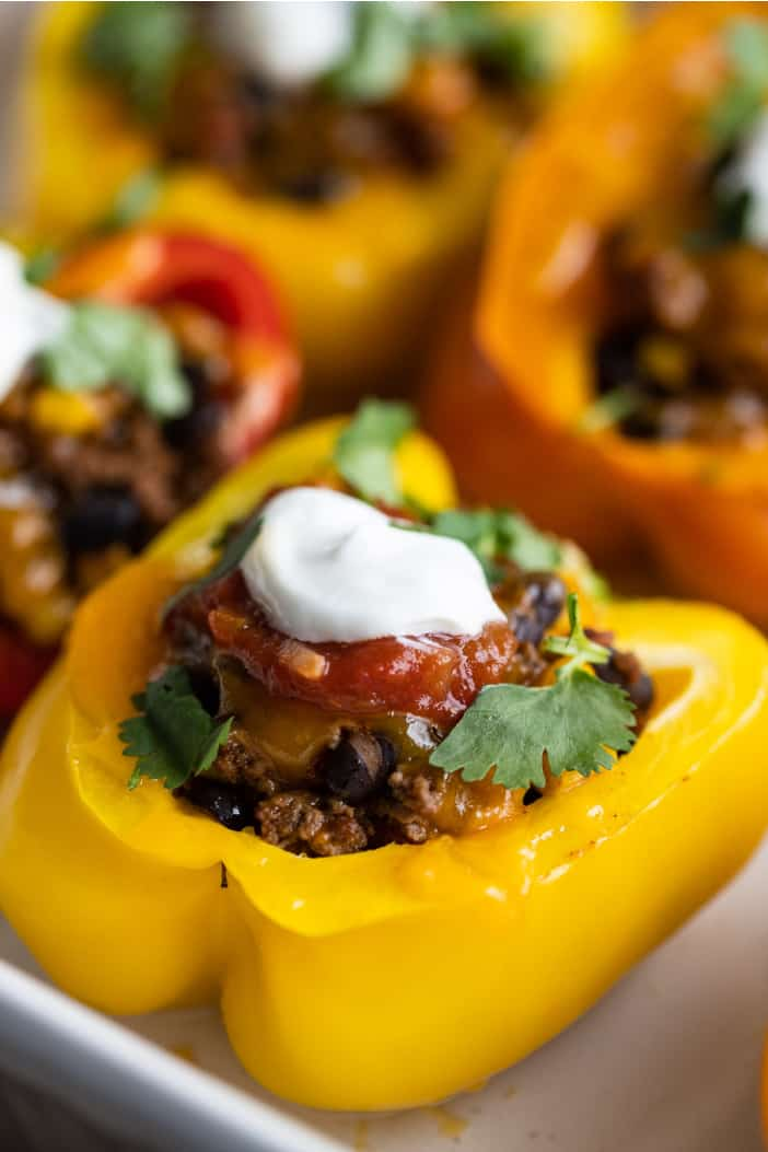 adding salsa and sour cream to the Mexican Stuffed Peppers