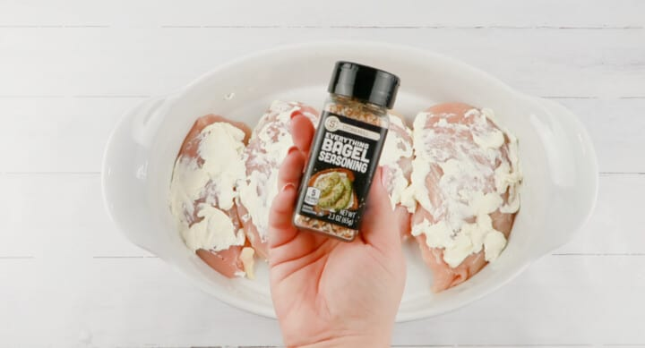 closeup of everything bagel seasoning jar with chicken in the background