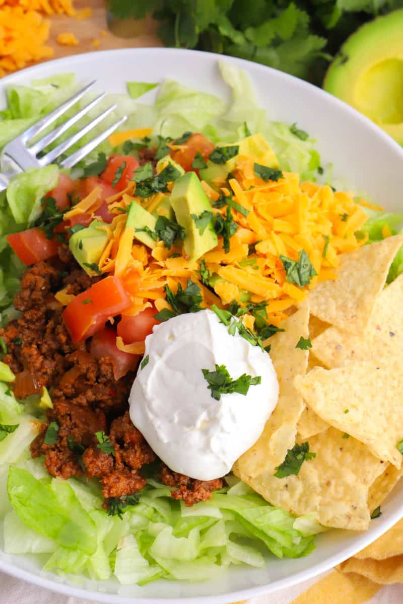 closeup of taco salad in white bowl with all the toppings