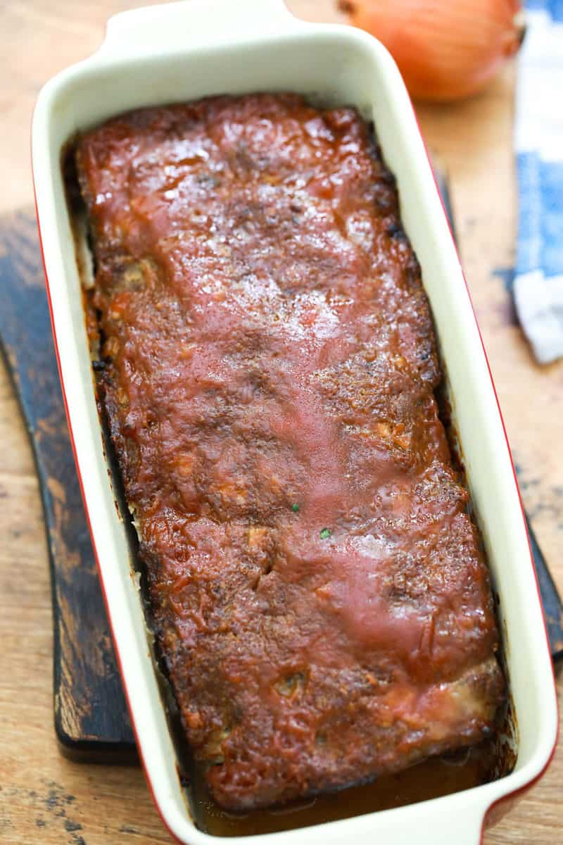cooked meatloaf in pan on wooden serving board