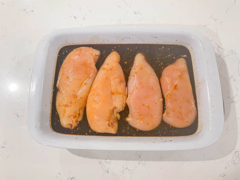 chicken breasts in baking pan with teriyaki sauce