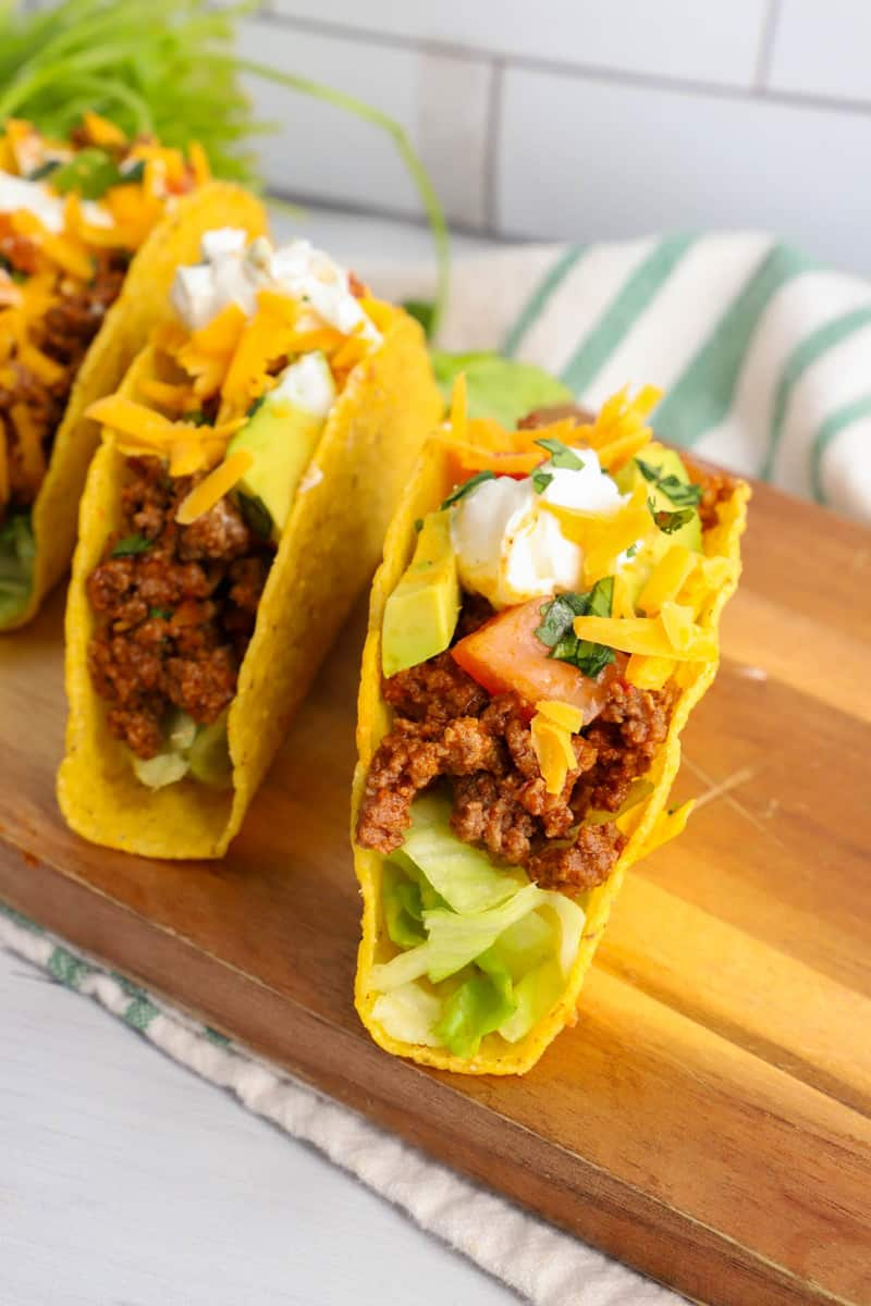 close up shot of completed tacos on wooden serving board