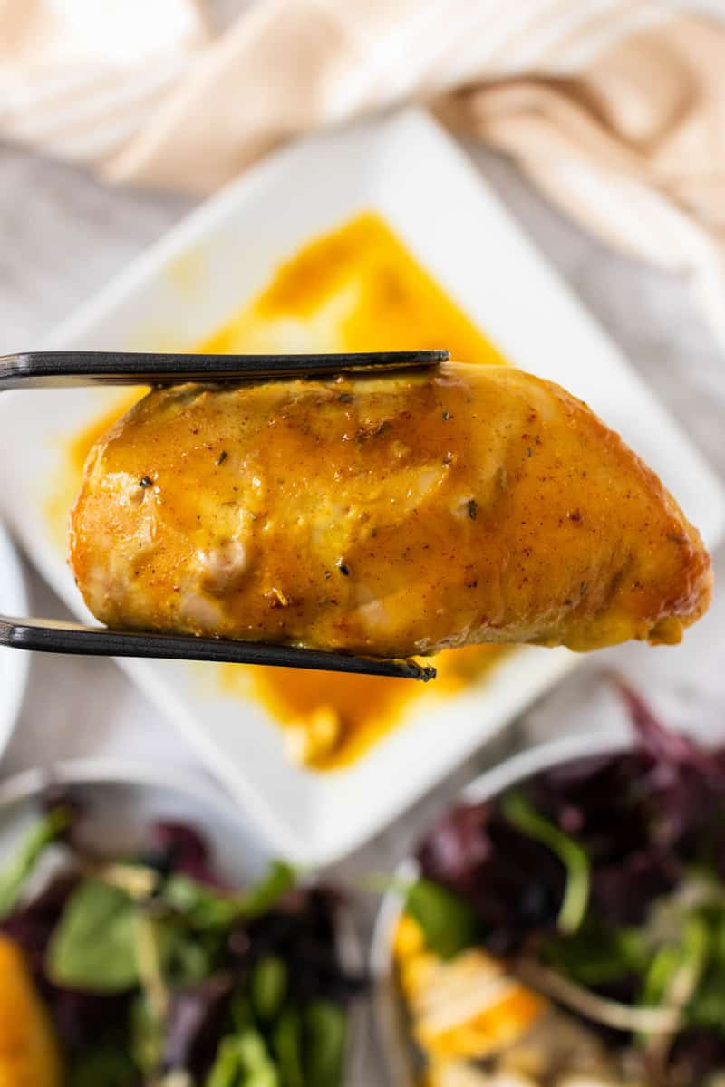 holding Honey Mustard Chicken with tongs
