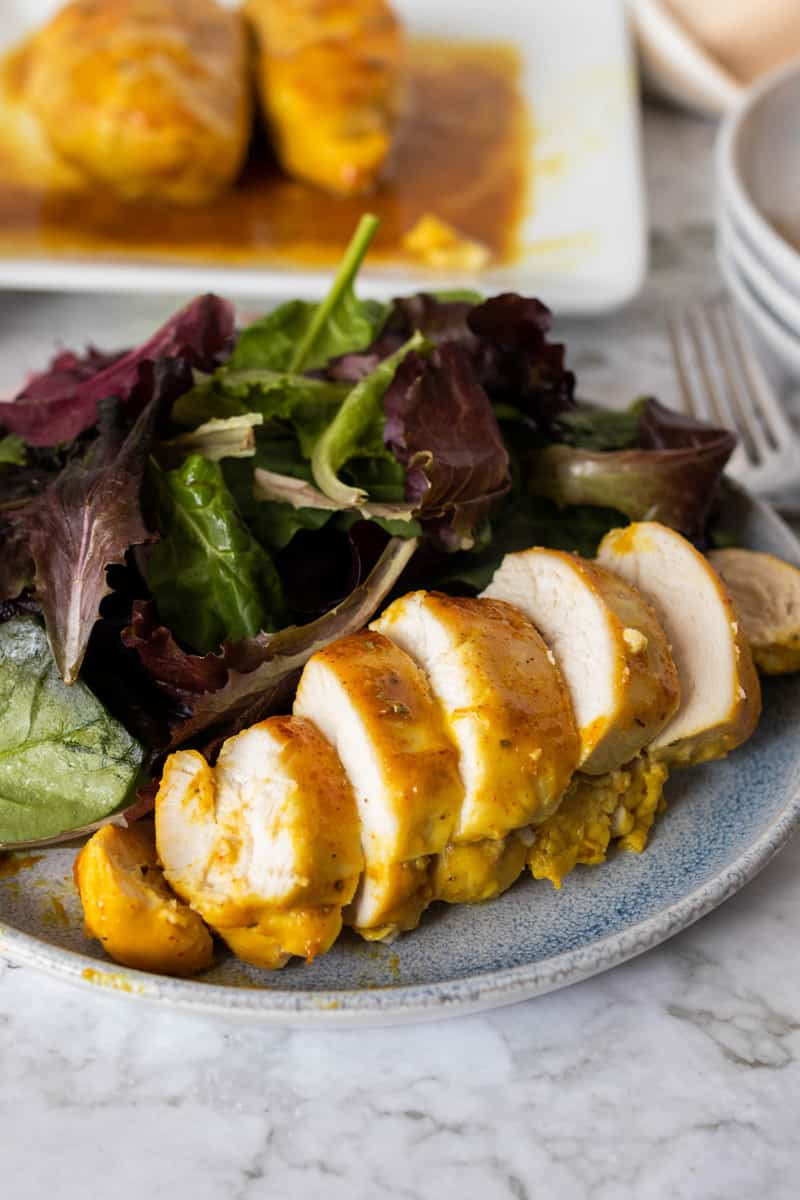 Honey Mustard Chicken sliced on a plate with salad