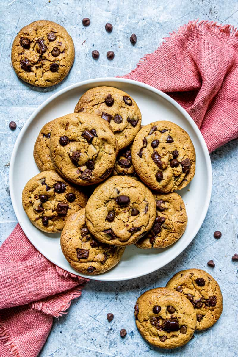 Brown Butter Chocolate Chip Cookies on white plate with red towel underneath