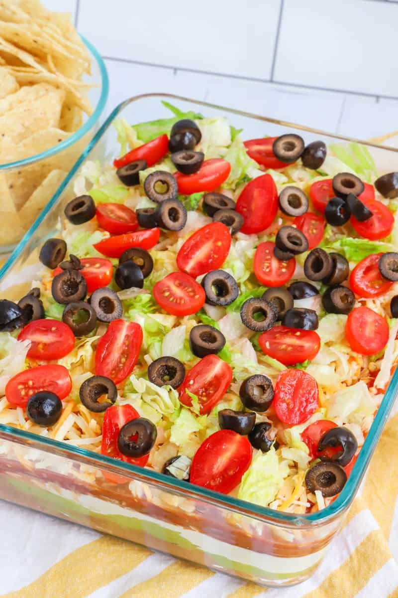Top down photo of 7 layer dip on a yellow and white striped towel