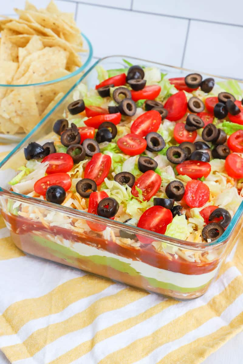 close up photo of 7 layer dip with tortilla chips in a bowl behind it