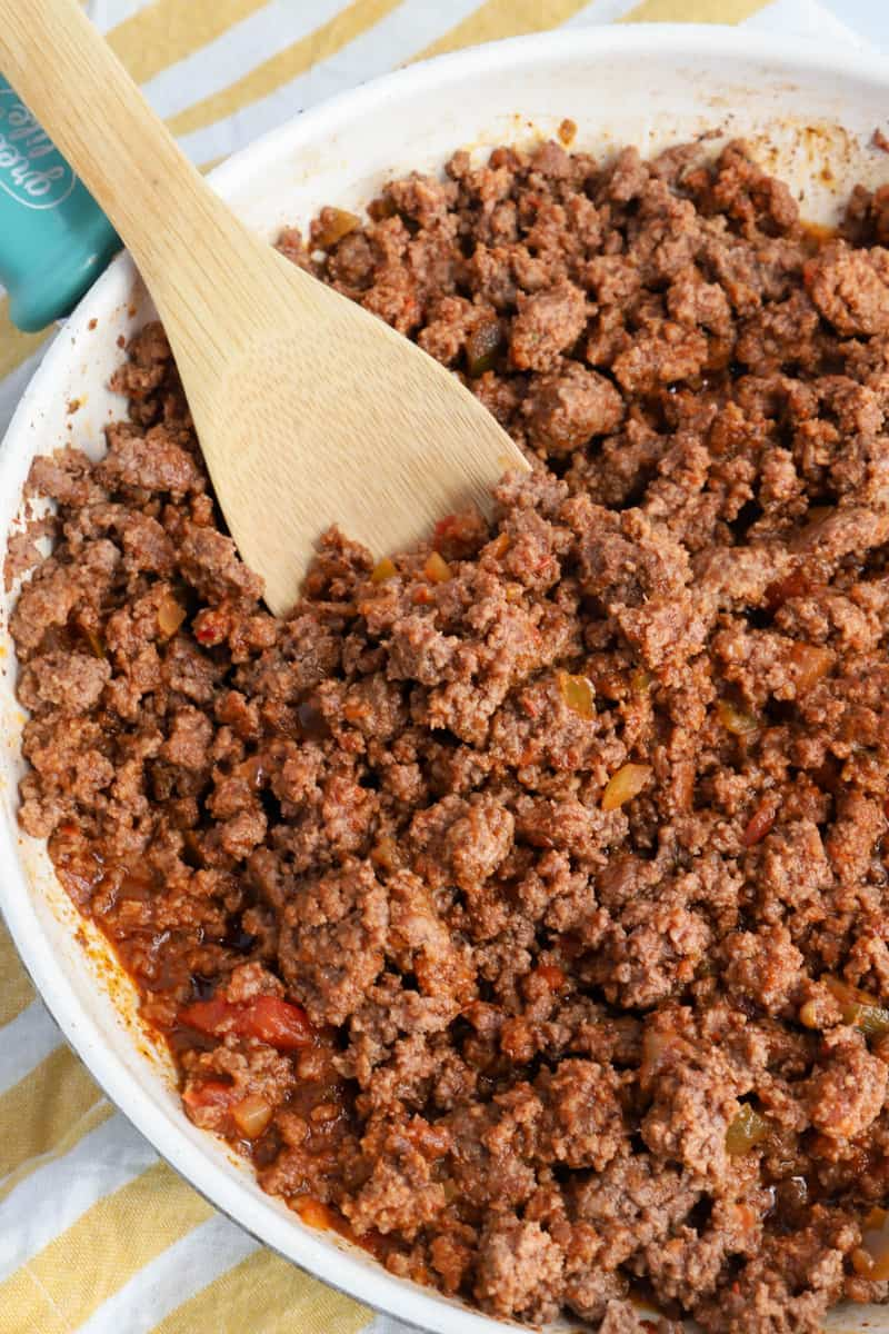 Taco Meat in a skillet with wooden spoon