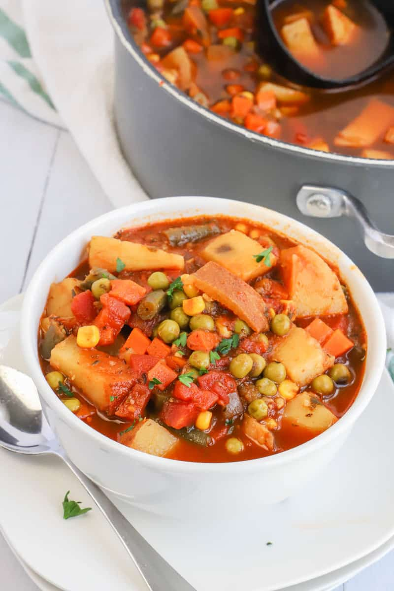 closeup photo of vegetable soup in white bowl on white plate