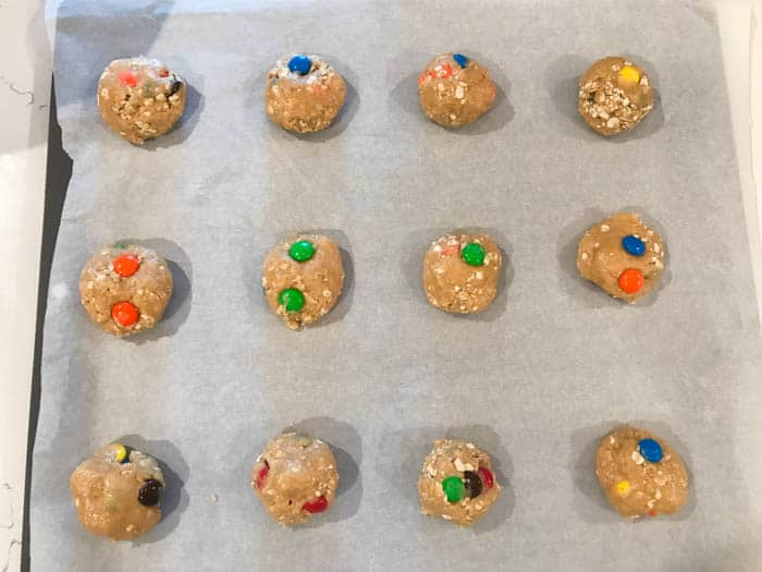 oatmeal M&M cookies on baking sheet with parchment paper