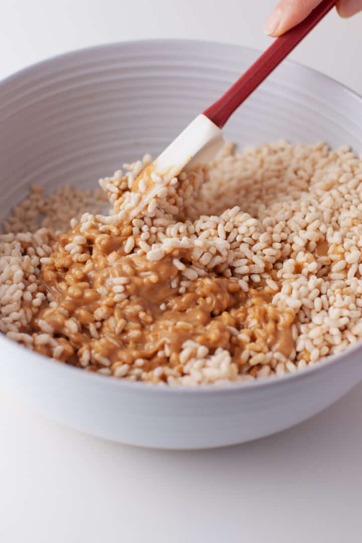 mixing up melted peanut butter with rice Krispies