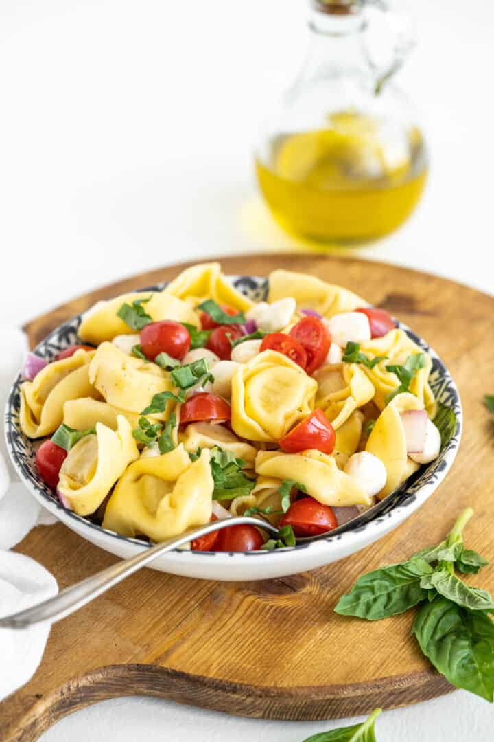 tortellini pasta salad in a bowl on a wooden serving board
