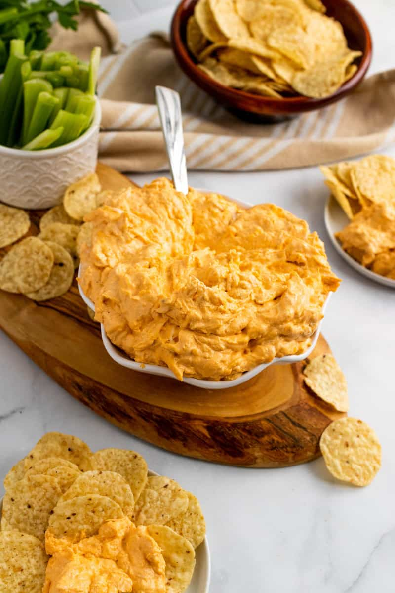 Buffalo Chicken Dip on wooden serving tray with tortilla chips and celery