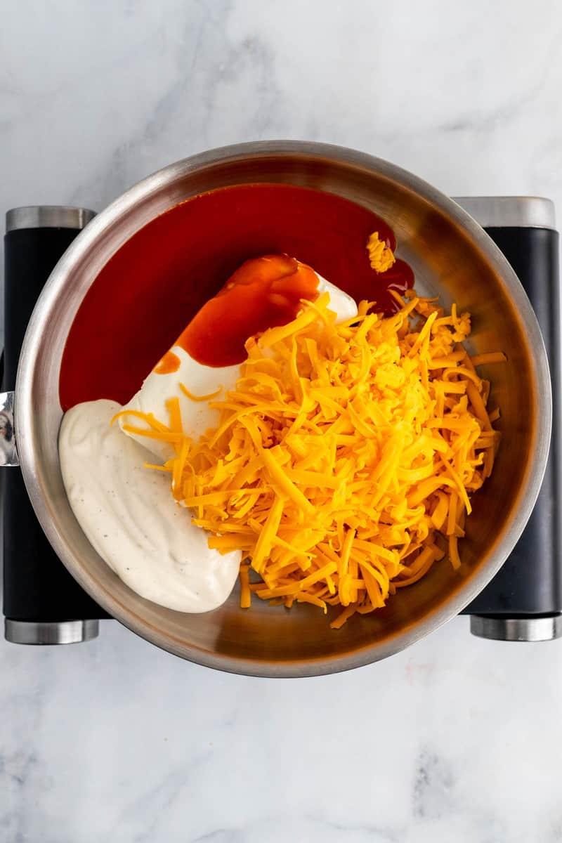 ingredients to make buffalo chicken dip in sauce pan