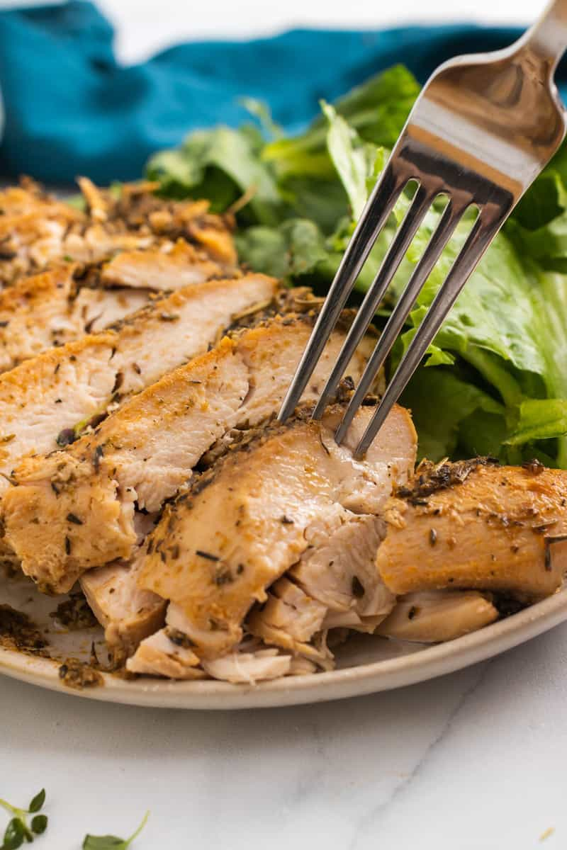 close up of sliced turkey breast being grabbed with a fork