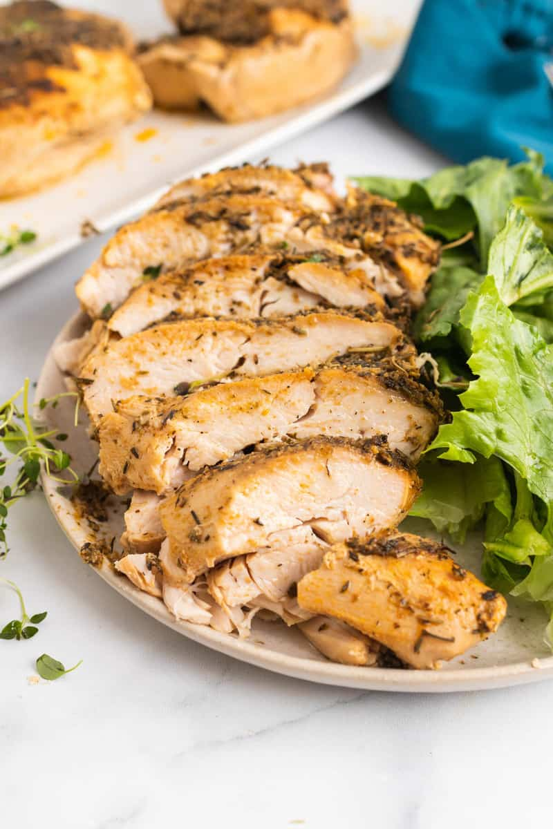 Slow Cooker Turkey Breast sliced on a plate with a salad