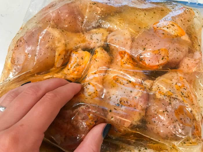 marinading the chicken in a large bag