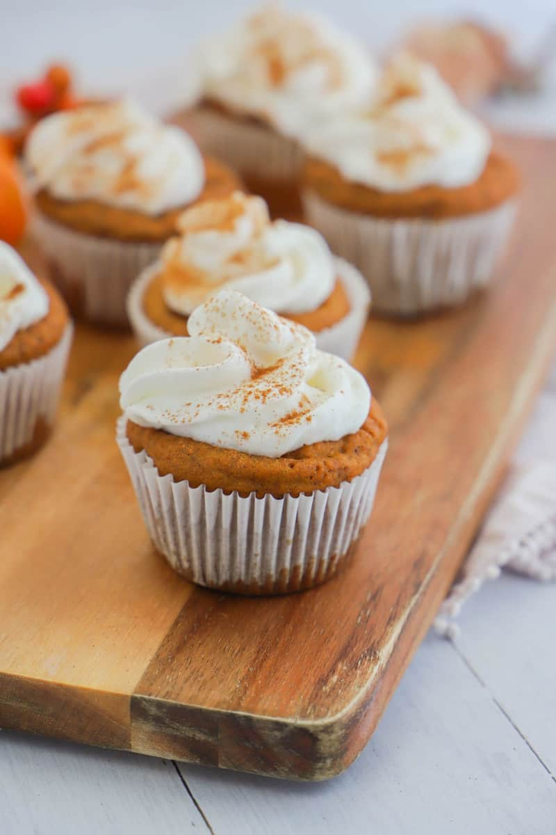 closeup of pumpkin cupcakes on wooden board topped with whipped cream