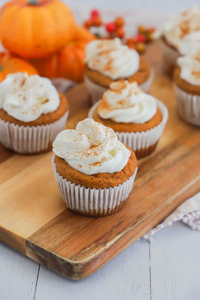 Pumpkin Pie Cupcakes topped with whipped cream on wooden serving board