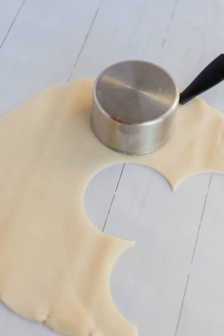 rolling out pie dough and cutting mini pie crusts