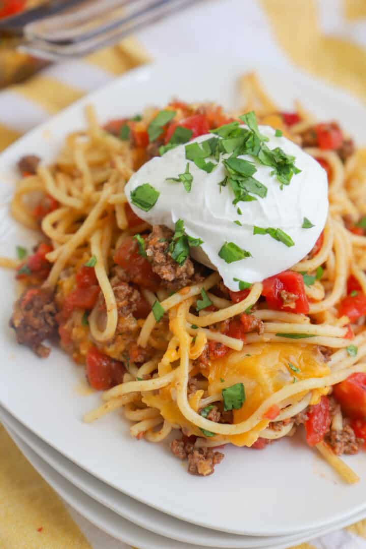 taco spaghetti on white plate topped with sour cream