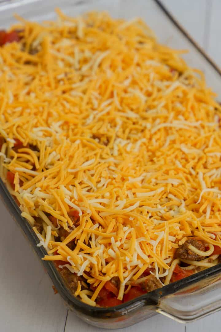 topping taco spaghetti casserole with cheese before baking