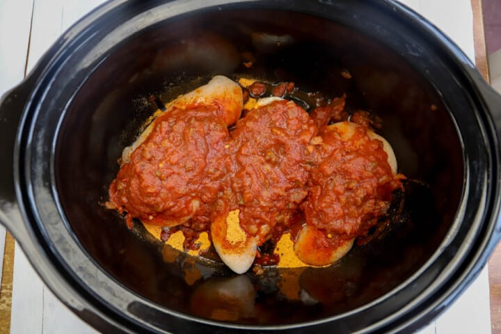 adding chicken salsa and other ingredients to slow cooker